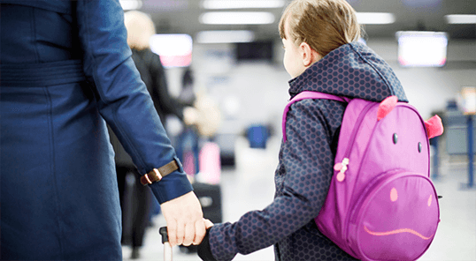 Young girl with a backpack and mother arriving at the airport.
