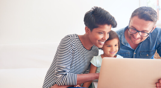 Couple and child looking at laptop